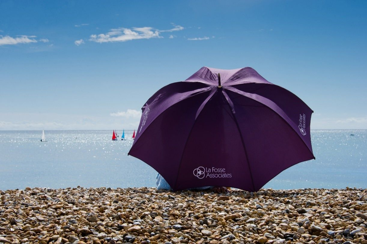 Someone sitting on a Cornish beach with the famous purple La Fosse branded umbrella